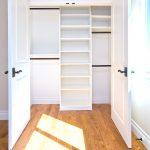 big walk in closet wood floor shelves doors window traditional bedroom