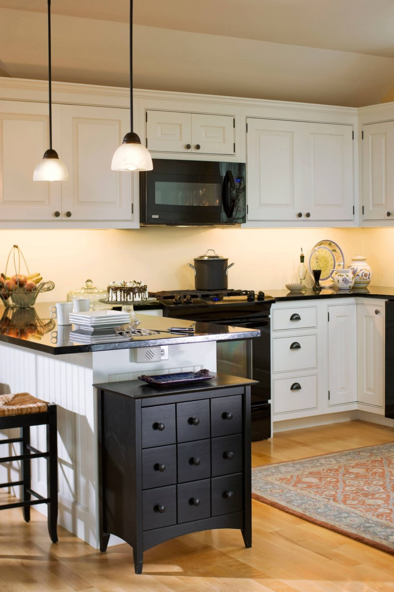 black appliances white cabinet black drawers black countertop ceiling lights area rug bar stool