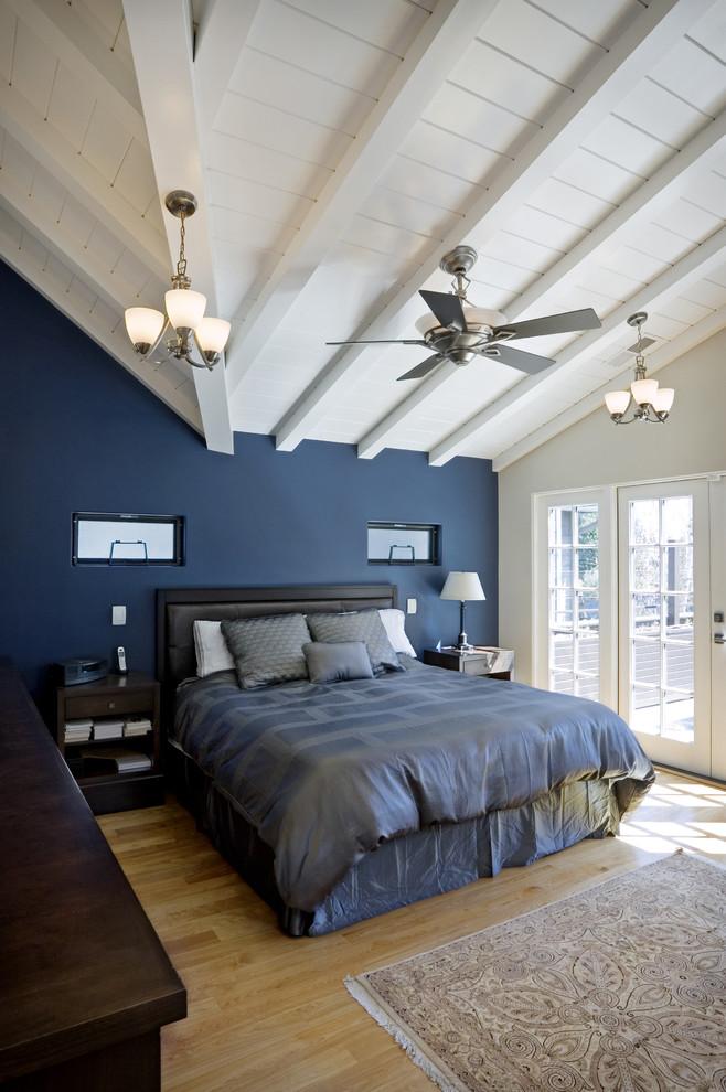 black bed frame with headboard navy blue walls white ceilings light hardwood floors light toned area rug dark hardwood bed side tables