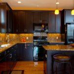 Black Cabinet Black Appliances Dark Bar Stool Granite Countertop Granite Backsplash Pendant Lights Light Wood Floor Built In Sink
