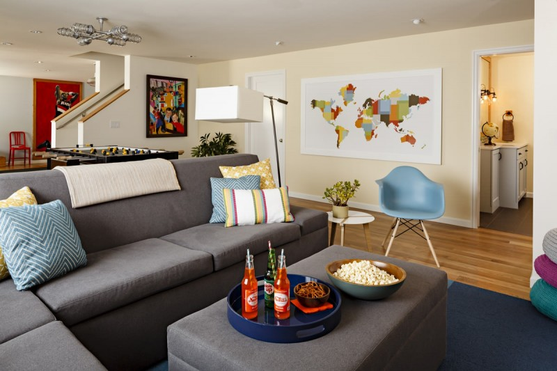 blue armchair grey sofa ottoman blue rug wooden floor floor lamp map wall mural industrial chandelier chevron pillow