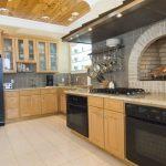 Brick Fireplace Tiled Backsplash Tiled Floor Black Appliances Light Wooden Cabinet Wooden Ceiling Recessed Lights Open Shelves Granite Countertop