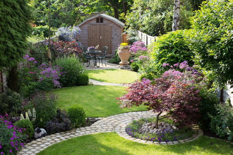circular walkway grass wooden hut purple flowers trees red flowers yellow flowers outdoor dining space