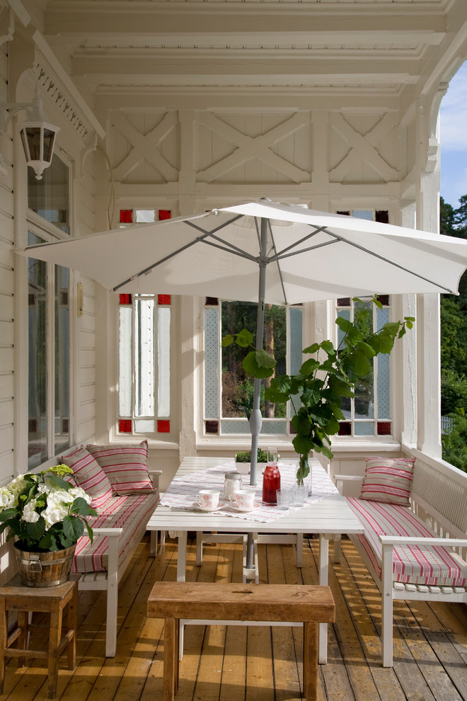 classic front porch idea painted in white IKEA table and bench sets with matching pillow throws white umbrella white table wooden deck floor
