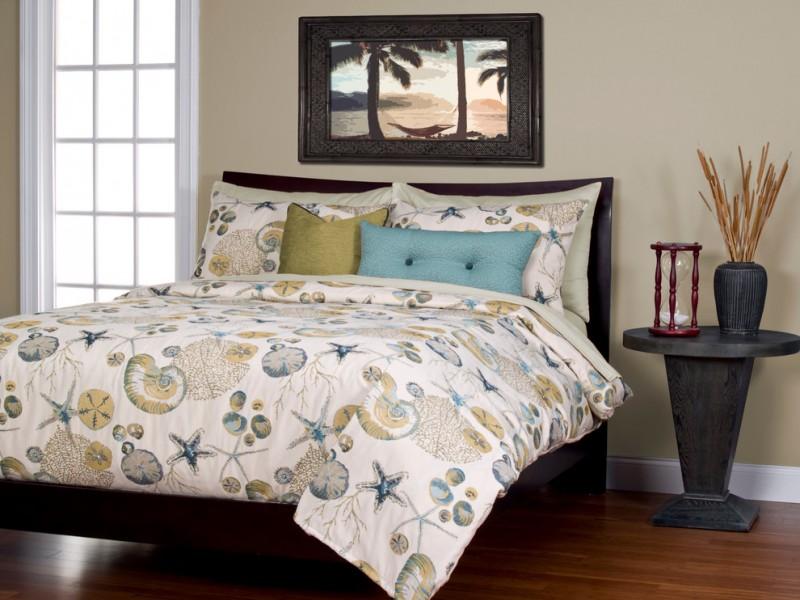 coastal style duvet and pillow cases dark hardwood bed frame with headboard dark hardwood bedside table medium tone wood floors light beige walls black framed beach painting