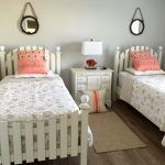 Coastal Style Teen Bedroom White & Textured Comforter With Printed Seashell Pictures In Grey Medium Toned Hardwood Floors Light Blue Walls A Pair Of Hung Mirrors