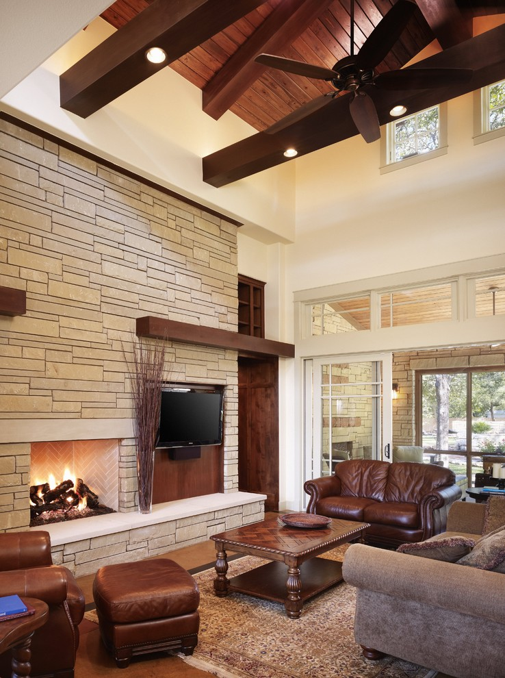 comfortable living room in mission style dark leather couches leather side chair dark hardwood center table grey couch with pillows wall mounted TV set recessed fireplace custom size tiles walls