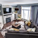 contemporary living room with sectional sofa pillows chairs carpet curtains lamp flowers wall tv storage space