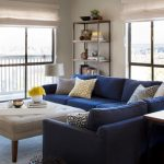 contemporary living room with sectional sofa table ottoman lamp shelves books windows