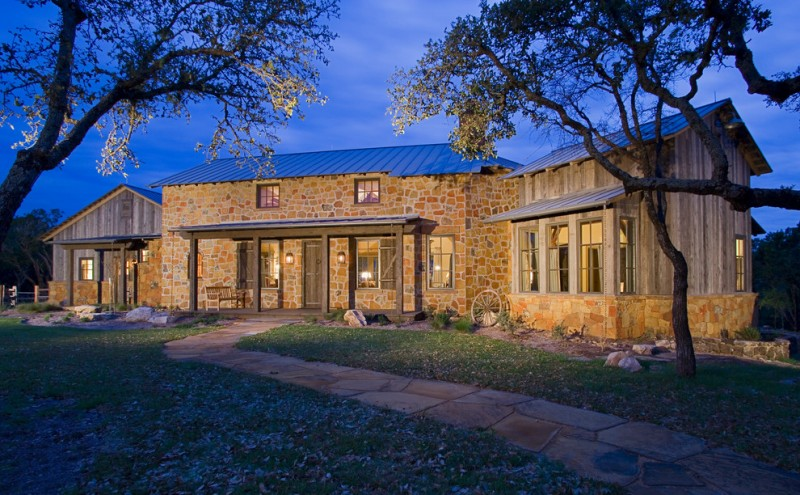 country home with rustic exterior with bare yellow stone on the wall, clad windows, wooden door, sconces