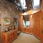 Craftsman Dressing Room With Wooden Walk In Closet Wooden Cabinets Exposed Stones Walls Free Standing Mirror Two Skylights