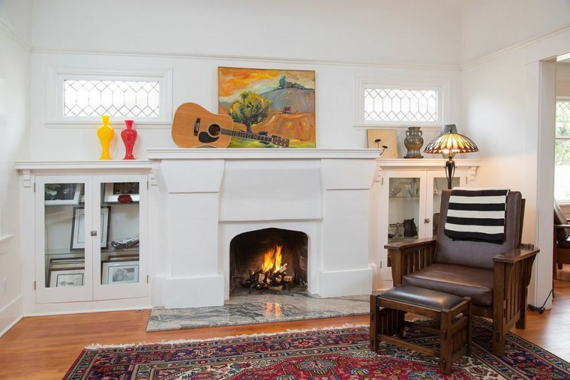 craftsman fireplace with white marble hearth dark hardwood chair with dark toned leather comforter small table with leather traditional area rug