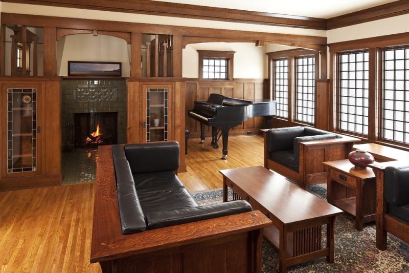craftsman open concept living room with music corner medium toned wood floors gray tiles fireplace dark wood wainscoting dark hardwood living room furniture