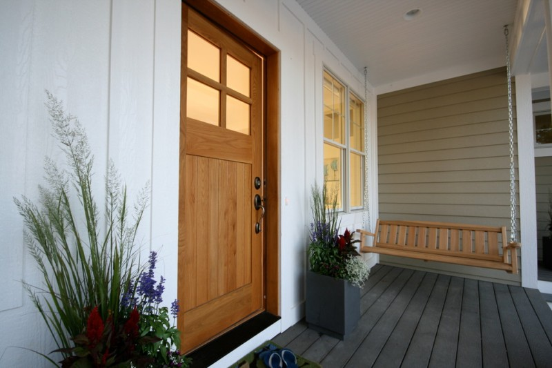 craftsman style front door dark floor hanging bench white wall decorative plants beach style entry