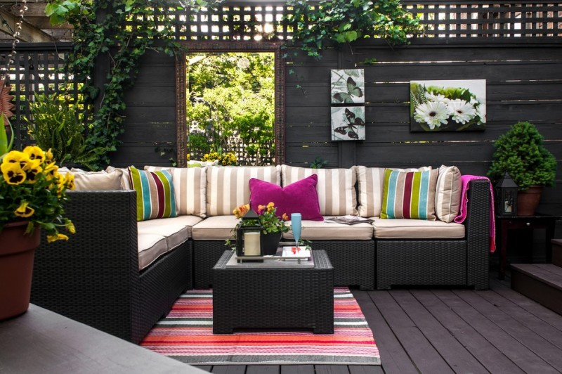 deck with black rattan with brown cushion stripped pillow, colorful stipped rugs, plants, hanging plants on fence, paintings