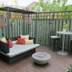 Deck With Green Painted Wood Fence, Rattan Day Bed With Blue Cushion, White High Table And Ratta Stool, Fire Pit, Hanging Decor