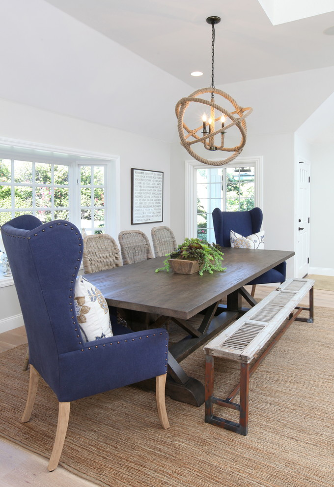 dining room table with bench and chairs carpet tall back chair chandelier windows decorative plant pillows beach style area