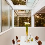 Dining Room With Retractable Glass Ceiling, Wide Frosted And Clear Glass Windows, White Table, Brown Chairs, Tall Flower Vase