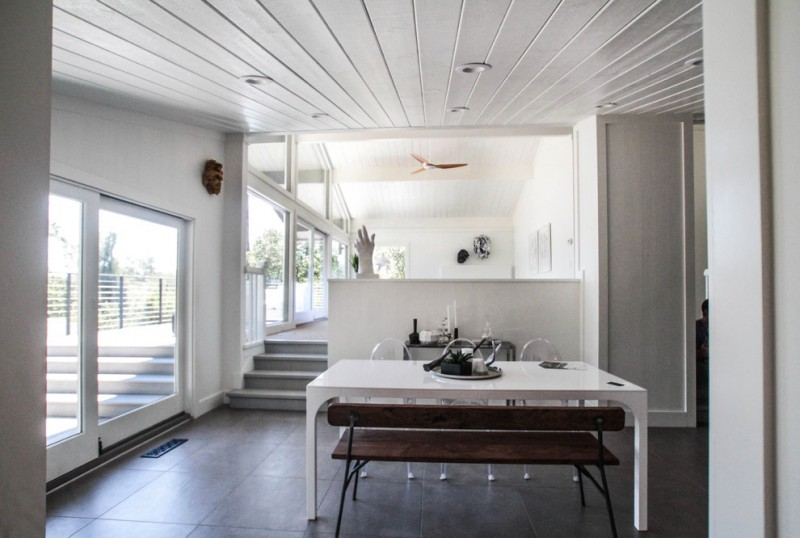 dining room with white wooden ceiling, glass sliding door, white table, white chairs, wooden bench, living room across the room