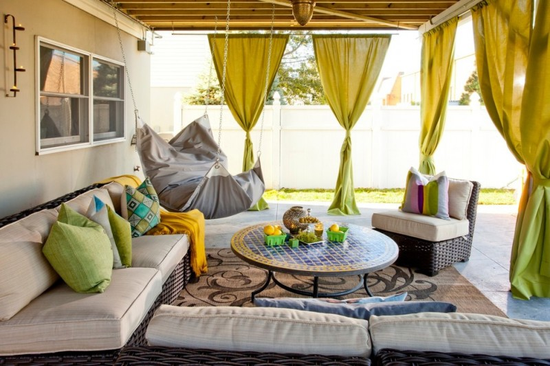 eclectic patio with green drapes on horizontal stick on the edge of the ceiling