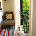 Enclosed Small Balcony With One Rattan Lounge Chair, Colorful Stripped Carpet, China Stool, Off White Curtain