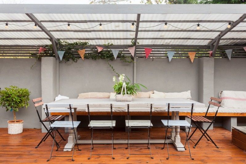 farmhouse patio with plastic awning repainted IKEA chairs in white light toned wooden floor white wall white table