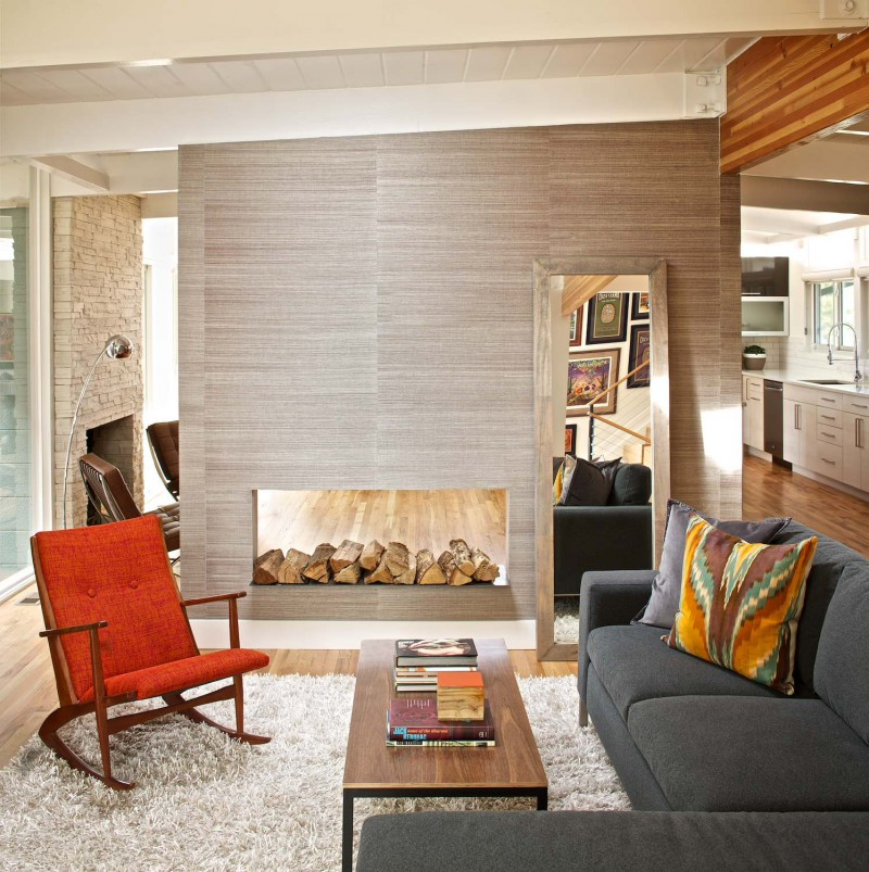 fireplace wall paper orange armchair grey sofa arc lamp area rug stone wall accent pillow wooden coffee table mirror