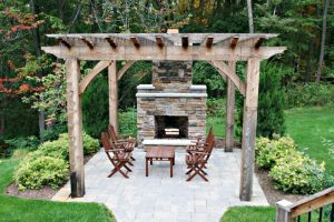 free standing patio in rustic shabby wooden pergola rock fireplace natural stone paving floors dark toned wood furniture