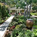 Front Yard Fountain Urn Garden Plants Stone Pavers Patio Chairs Table Door Windows Traditional Design