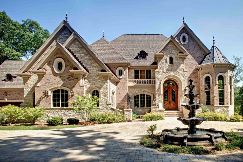 front yard fountains gable roofs large windows stone walls pavers garden traditional design