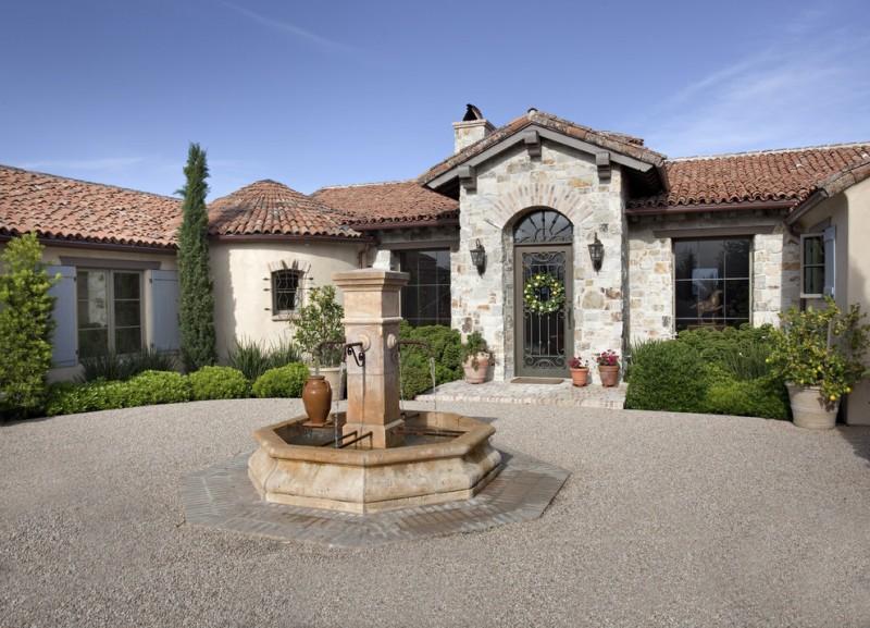 front yard fountains sconces stone walls pavers pond windows metal door chimney urn mediterranean design
