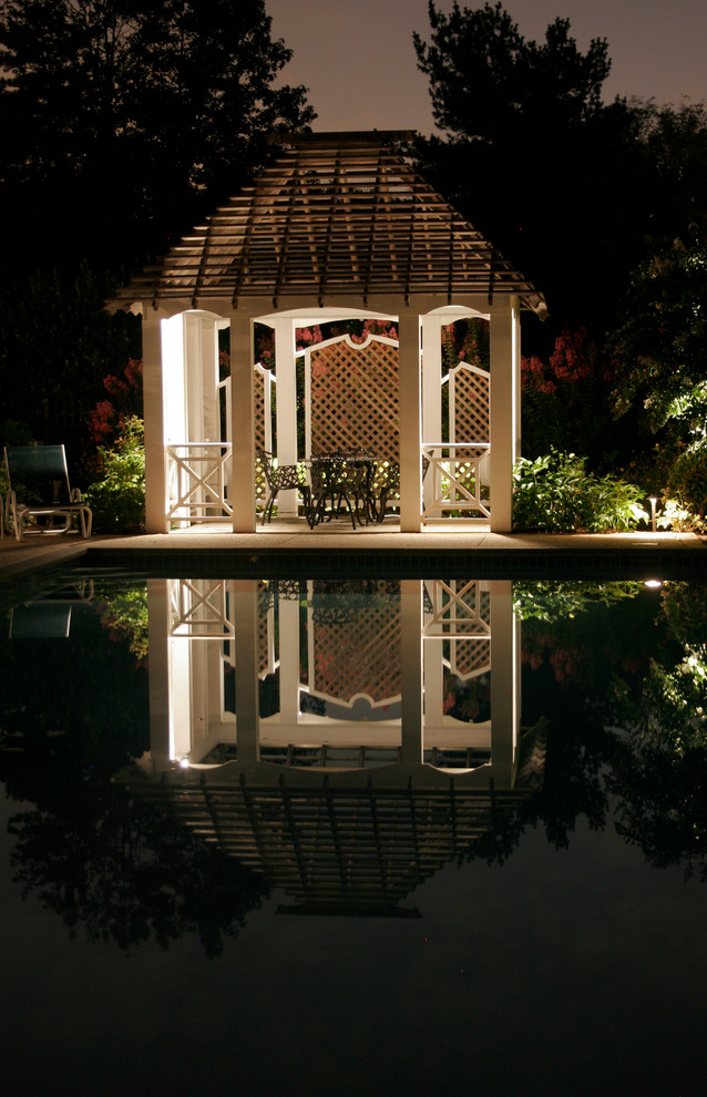 gazebo beside pool with white wooden poles and rails, black chairs set, wooden nets partitions, wooden nets roof