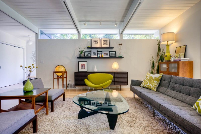 glass coffee table grey couch area rug green armchair dark credenza floating shelves wall cabinet planthouse sloped ceiling