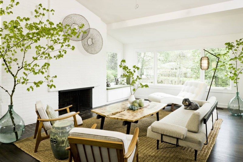glass vase house branches armchair sofa chaise lounge white wall brick wall fireplace darkwood floor area rug wooden coffee table