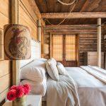 hanging lights in bedroom double bed sidetable rustic rope headboard wood wall ceiling carpet