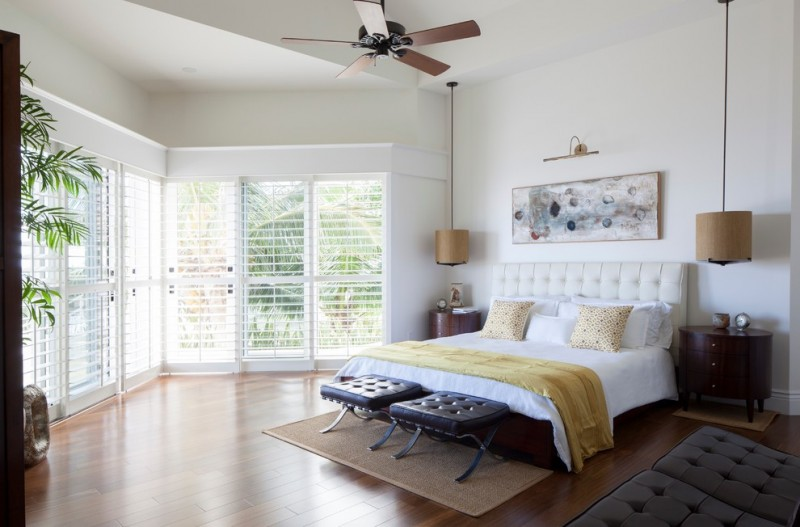 hanging lights in bedroom hardwood floors leather tufted ottomans window wall blinds ceiling fan double bed hardwood floors sidetables artwork tropical style