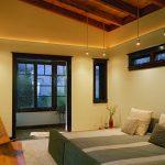 hanging lights in bedroom wood chair hardwood floor double bed bedding pillows carpet sidetable door windows contemporary design