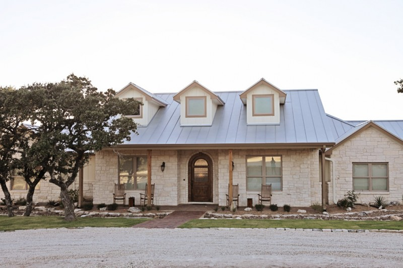 hill country home exterior with limestone wall, wooden door, sconces, blue roof