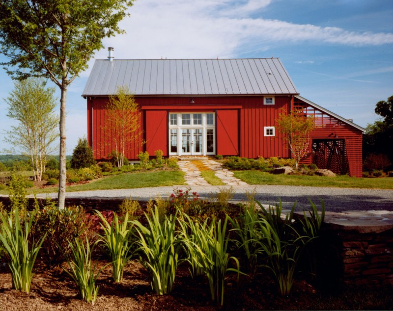 houses that look like barns door small windows roof red wall trees grass farmhouse exterior