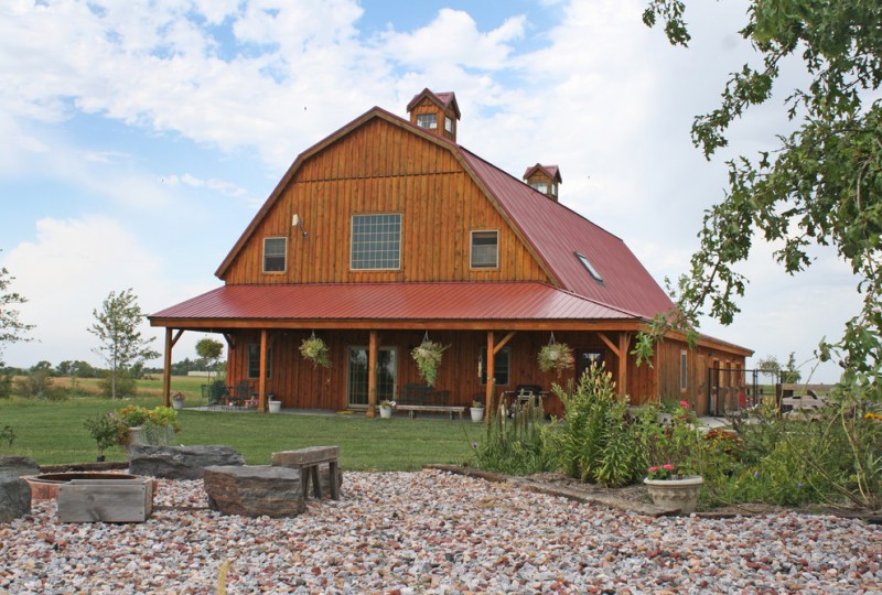 houses that look like barns windows pillars decorative plants seating rocks flowers farmhouse exterior