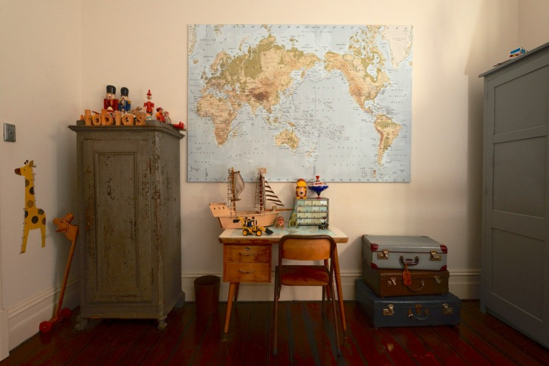 kids bedroom with vintage cupboard, vintage suitcase, vintage small study table and chair, world map