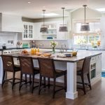 kitchen island with seating for 4 farmhouse sink shaker cabinet brown countertops chairs ceiling lights subway tile backsplash pendants garden window rug hardwood floors beach style