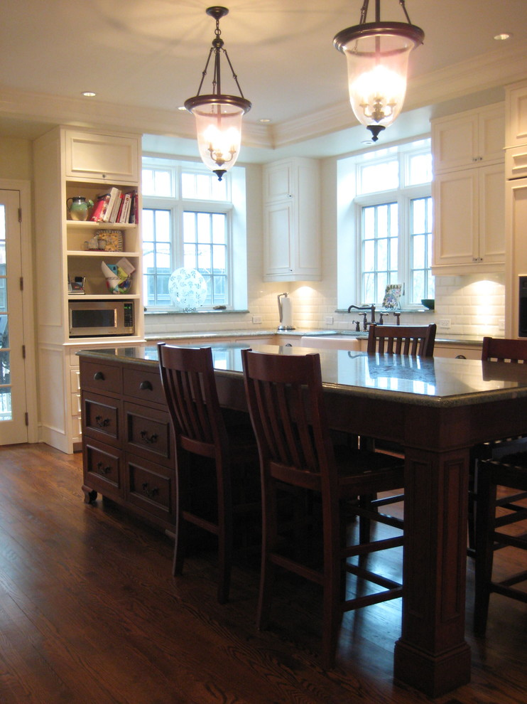 kitchen island with seating for 4 pendants brown countertops white cabinets hardwood floors chairs sink subway tile backsplash shelves traditional design