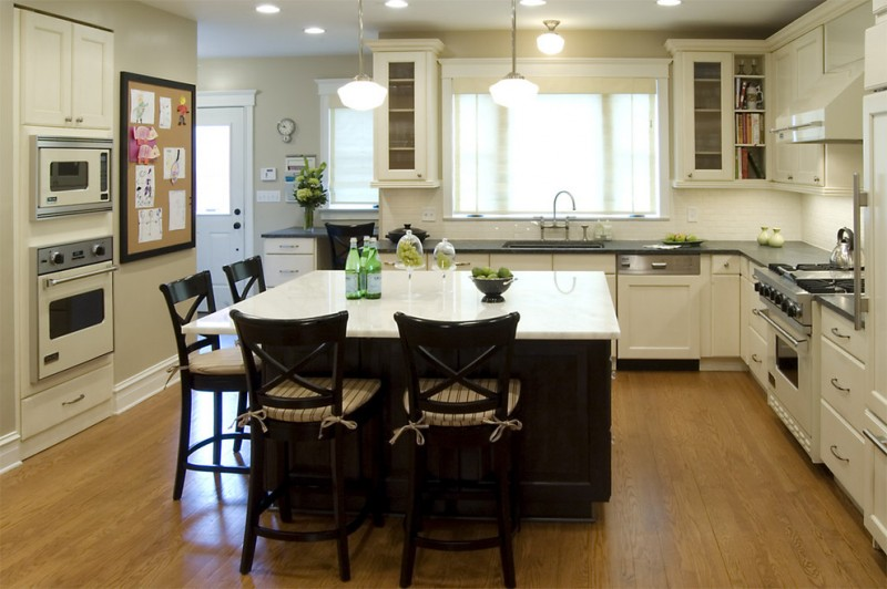 kitchen island with seating for 4 soapstone countertops hardwood floors glass front cabinets sink white backsplash chairs pendants ceiling lights traditional design