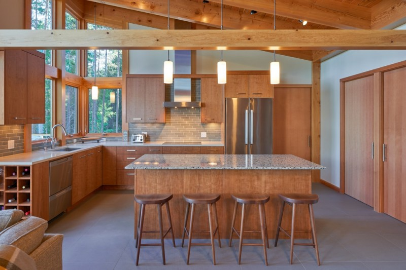 kitchen island with seating for 4 solid surface countertop flat panel cabinets sink ceramic backsplash concrete floors stools sink pendants stainless steel appliances contemporary design