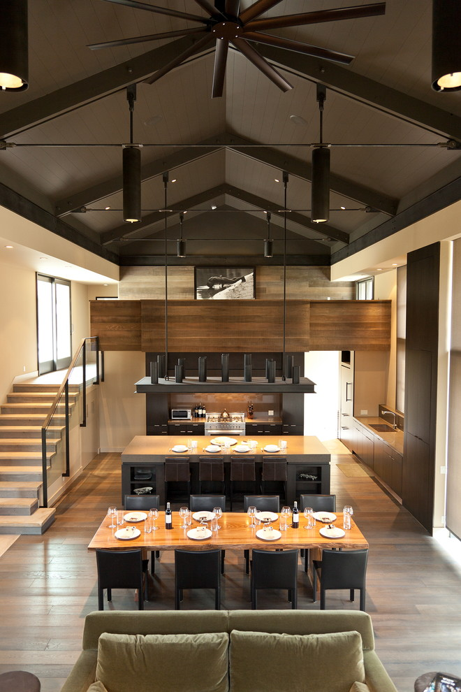 kitchen island with seating for 4 wood countertop dining table stools flat panel cabinets brown backsplash sink chairs sofa stairs hardwood floors contemporary design