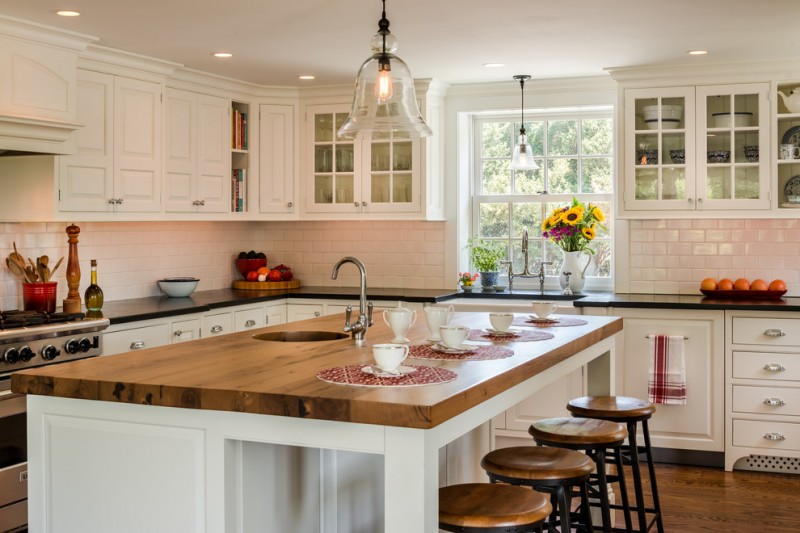 kitchen island with seating for 4 wood countertop farmhouse sink glass front cabinets hardwood floors white backsplash ceiling lights stools pendants stainless steel appliances farmhouse design
