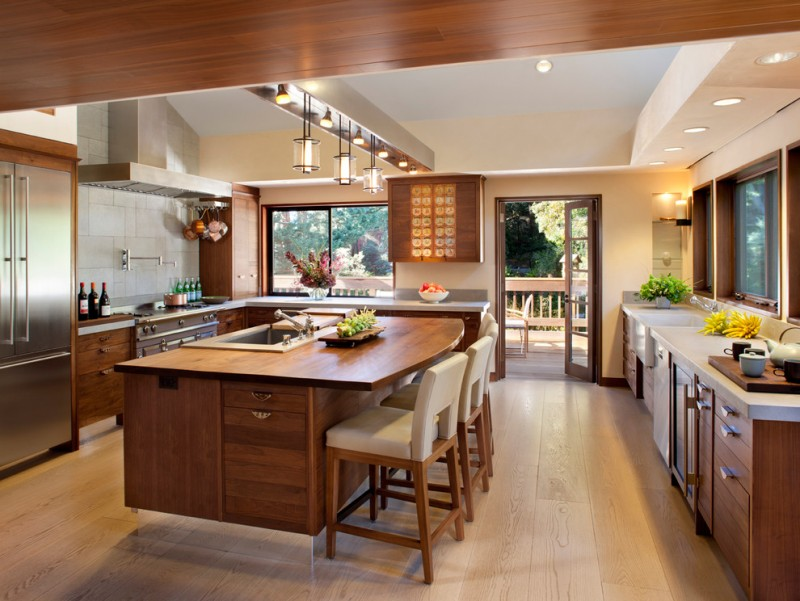 kitchen island with seating for 4 wood countertop flat panel cabinets drop in sink grey backsplash ceiling lights pendants stools windows hardwood floors stainless steel appliances transtional design