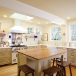 Kitchen Island With Seating For 4 Wood Countertop Raised Panel Cabinets Ceiling Lights Hardwood Floors Hanging Shelves Stools Sink White Backsplash Traditional Design