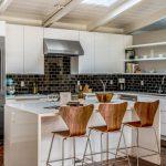 Kitchen With White Sleek Island, Wooden Stool, Black Tiles Backsplash, White Sleek Cabinet And Shelves